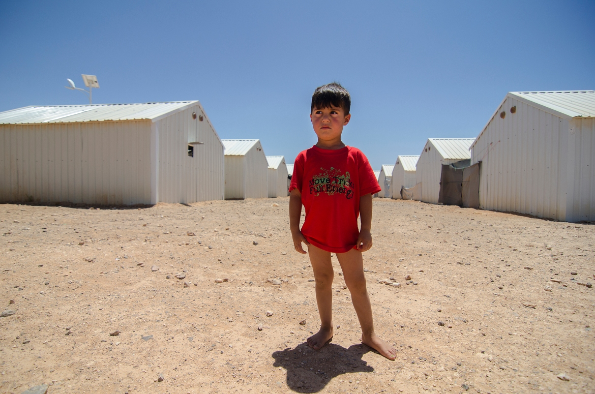 A Syrian  child stands among metal shelters in Azraq's Village 6, one of two 'villages' that are populated inside the desert camp. [Alisa Reznick/Al Jazeera]
