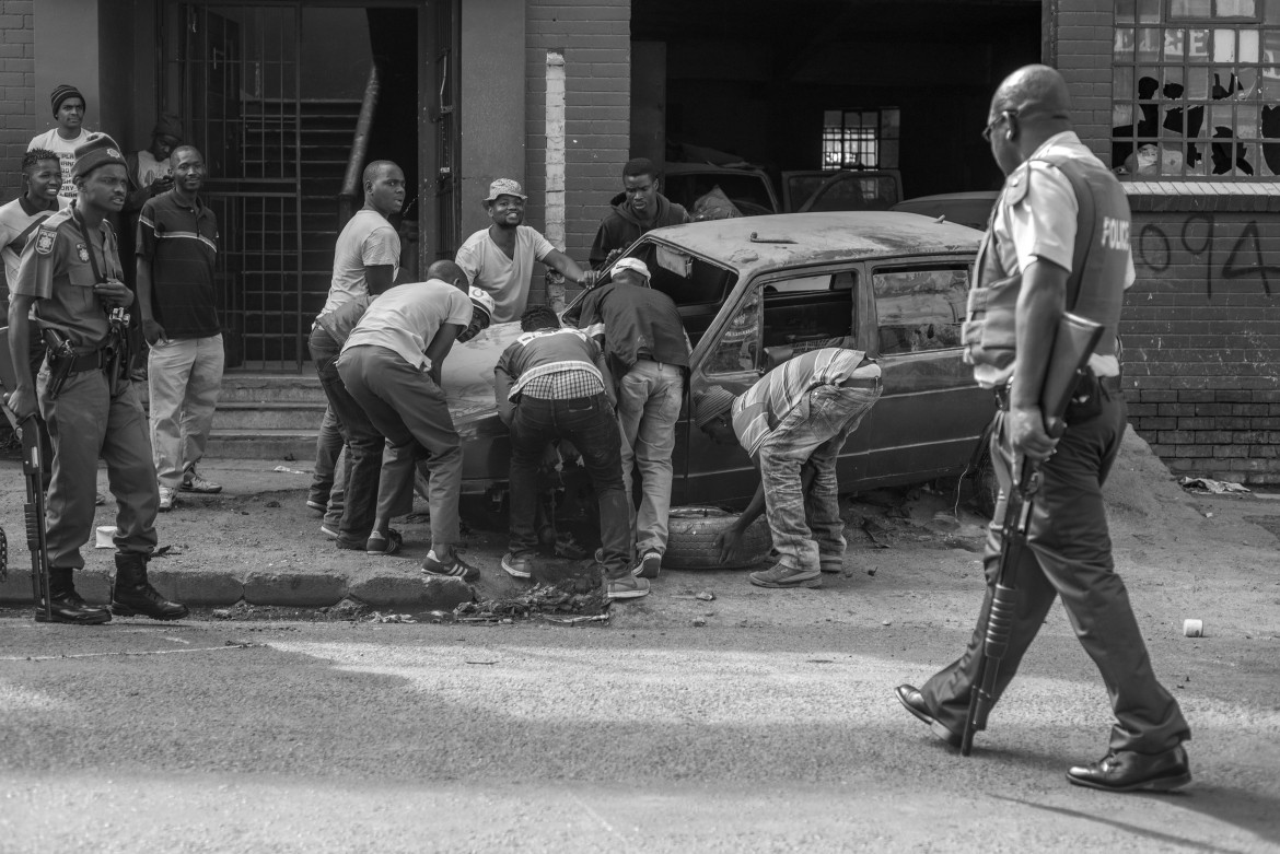 Members of the South African police stand guard as a group of Nigerian men try to salvage a car from their vehicle repair shop which was set on fire by mobs. The entire workshop was destroyed along with most of the cars parked inside. [Ihsaan Haffejee/Al Jazeera]