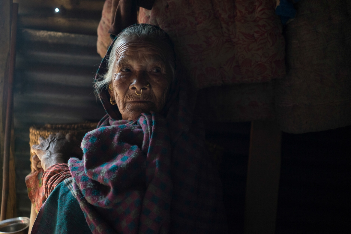 Antari Maya Jimba, born in 1933, rests inside the shelter made of salvaged corrugated iron roofing that her family constructed in the village of Jhankridanda, Lalitpur District. Antari Maya wasn't able to flee the quake and was partially buried in rubble when the home she was inside collapsed. Her grandson pulled her free of the ruins and she sustained no significant injuries. [Brian Sokol/Al Jazeera]