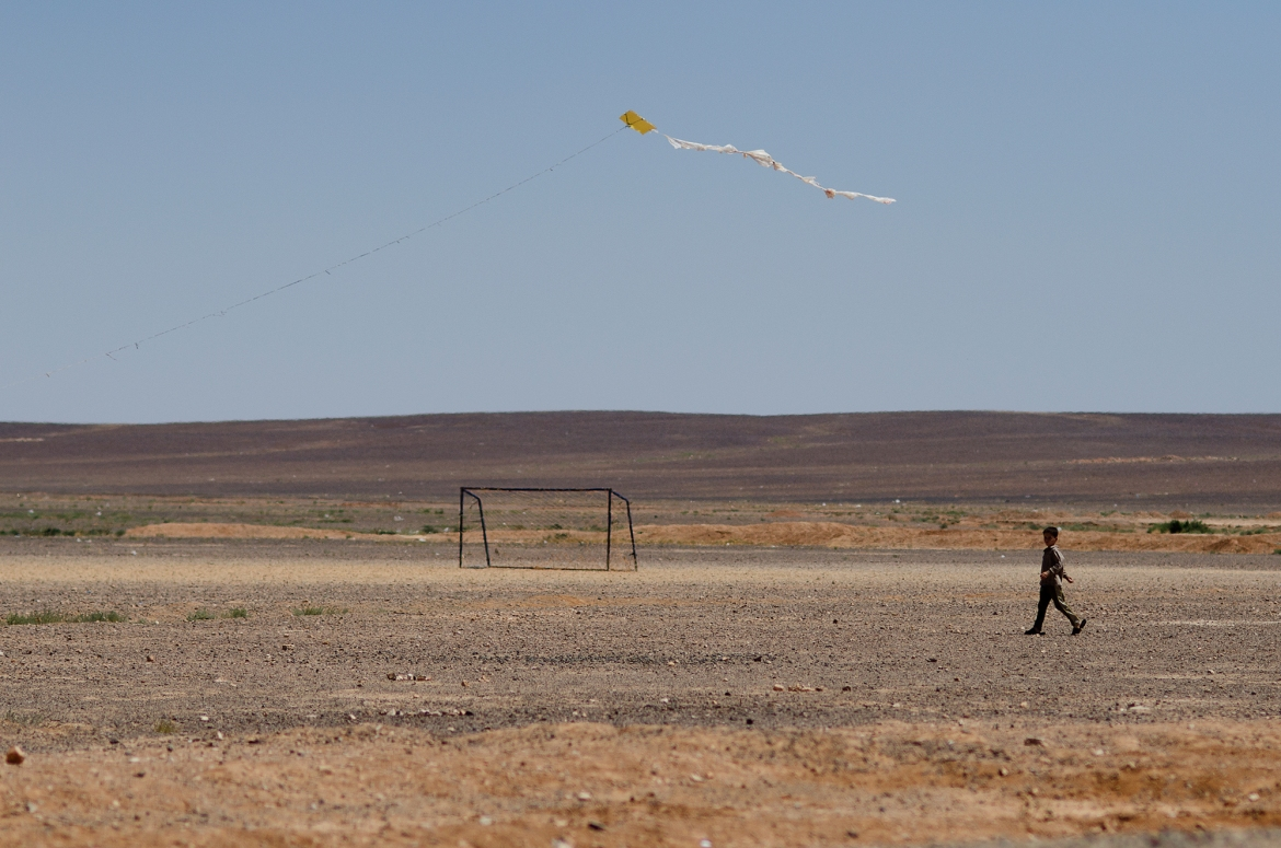 A young Syrian refugee follows a kite on the outskirts of Azraq. [Alisa Reznick/Al Jazeera]