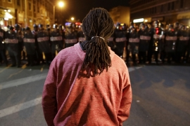A protester watches as police enforce curfew in Baltimore [AP]