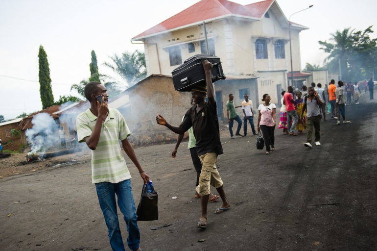 A man carries his belongings from the Mugasa neighbourhood, which has been wracked by protests. Tens of thousands have fled the country. [Phil Moore/Al Jazeera]