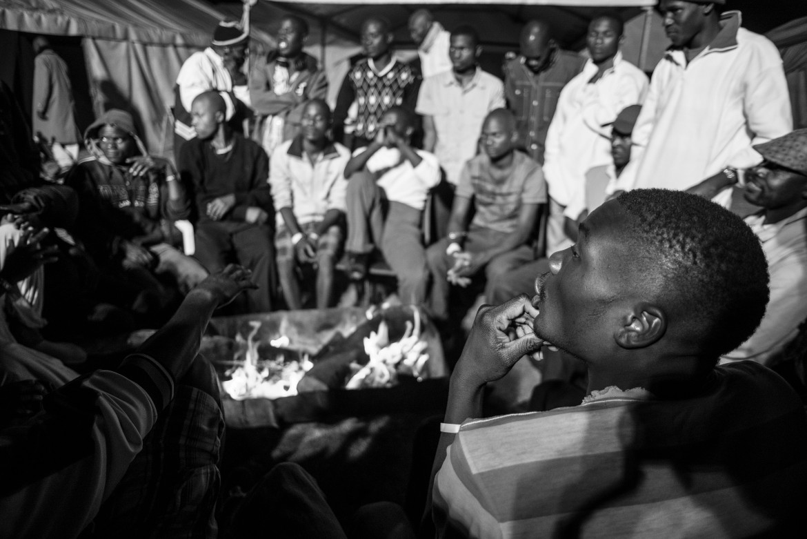 Migrants from Malawi who fled their homes in wake of the attacks sit around a fire at a camp set up in Mayfair. [Ihsaan Haffejee/Al Jazeera]