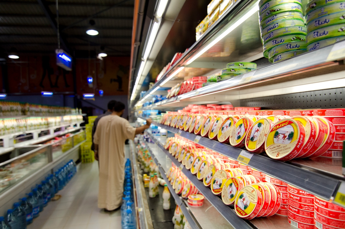 Shoppers browse fresh dairy products inside Azraq's only supermarket. Residents say food prices have soared in recent months, with basic items increasingly outside of the budget allotted to each refugee through a food voucher system. [Alisa Reznick/Al Jazeera]
