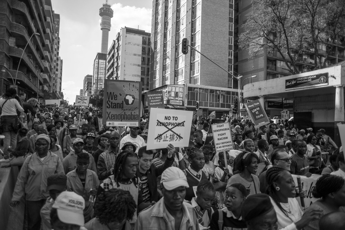 People hold up signs during a large anti-xenophobia rally in Johannesburg which was attended by thousands. [Ihsaan Haffejee/Al Jazeera]