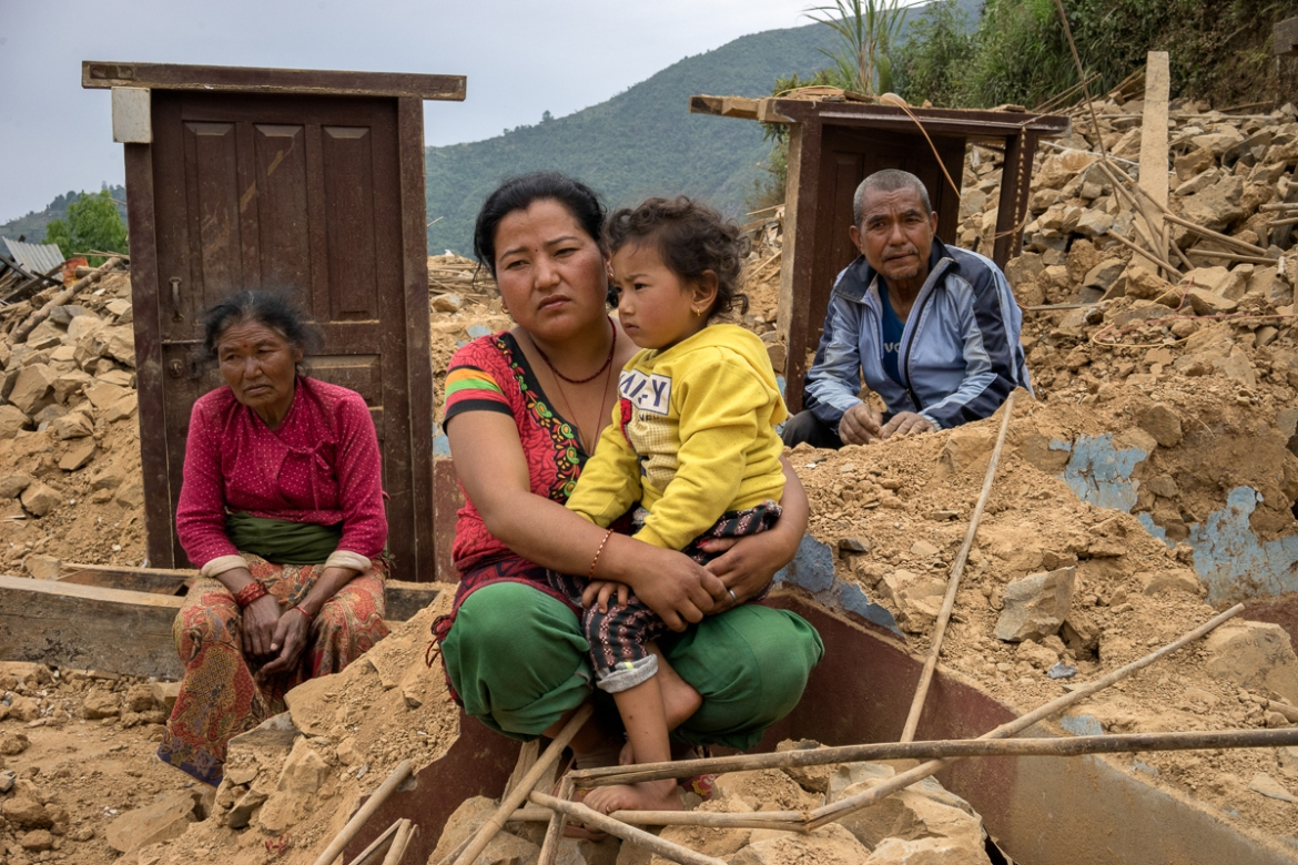 The family of Dan Bahadur Tamang, 66, right, sits in the rubble of their family's home in the village of Jhankridanda, Lalitpur District. Nepal's government estimates reconstruction costs of $7bn, a third of the country's GDP. [Brian Sokol/Al Jazeera]