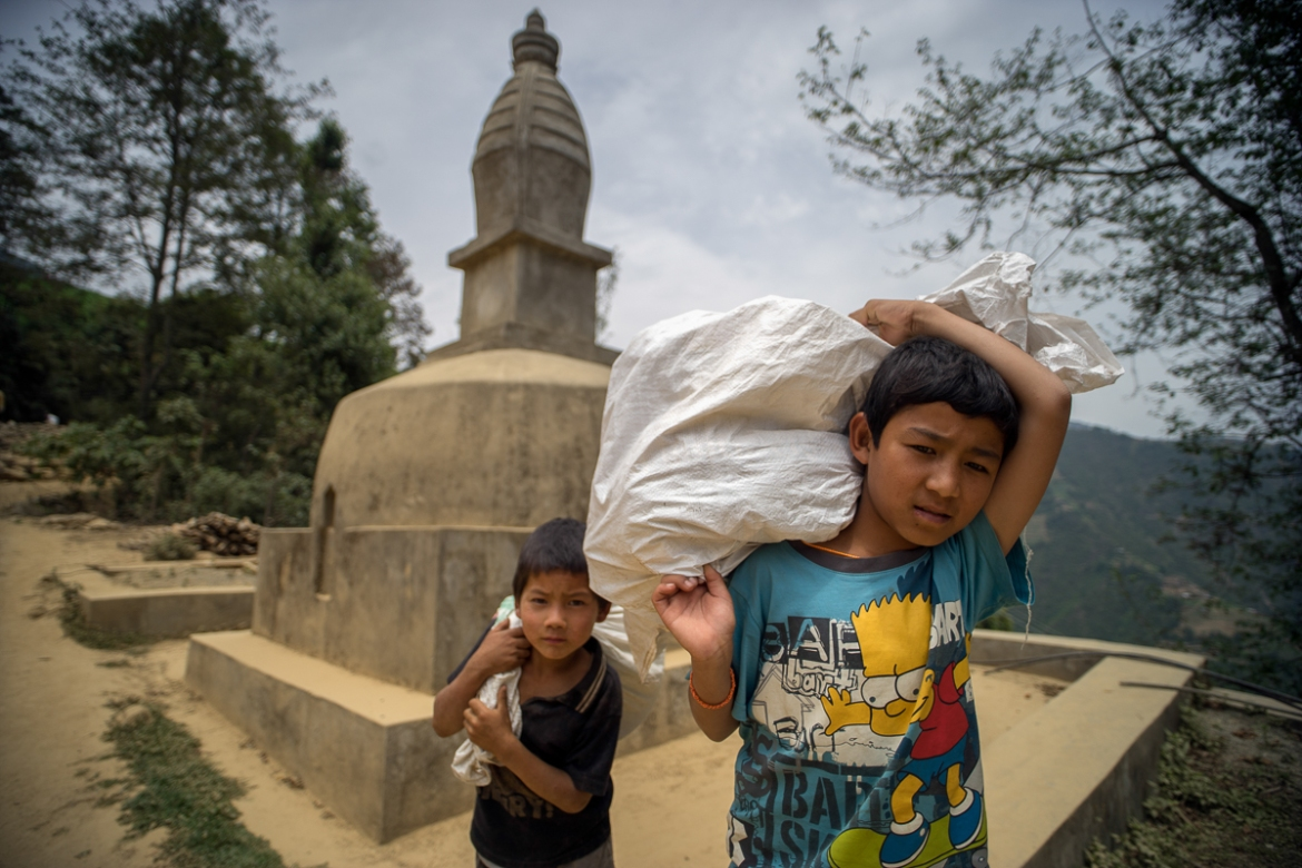 Sarod Tamang, 12, right, and Ramesh Ghalan, 7, carry bags of relief supplies past a Buddhist stupa, following aid distribution in the village of Jhankridanda, Lalitpur District. With the monsoon approaching, the situation is likely to deteriorate in the coming weeks, and far more assistance is rapidly needed. [Brian Sokol/Al Jazeera]