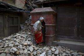 A woman walks on the debris from a collapsed house a month after the earthquake in Kathmandu, Nepal [REUTERS]