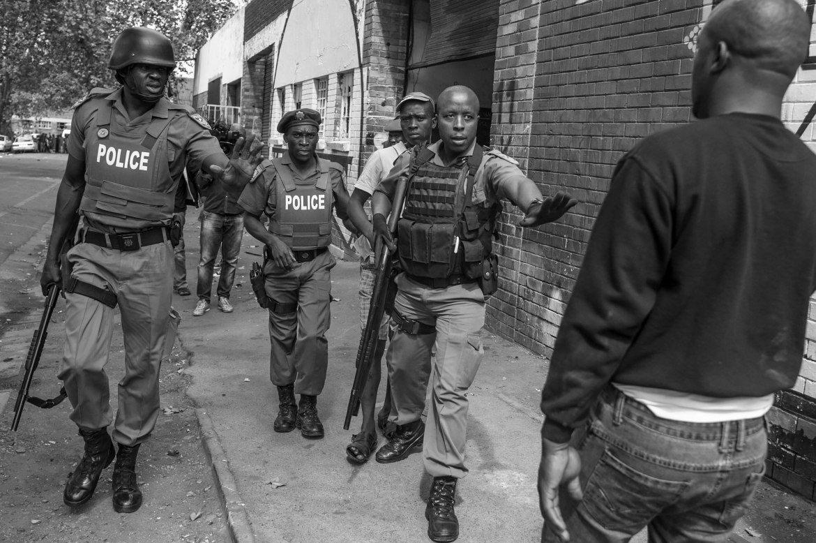 Police hold out their hands to prevent a Nigerian man from approaching a South African who had been arrested while looting a Nigerian-owned business in the Johannesburg suburb of Jeppestown. [Ihsaan Haffejee/Al Jazeera]