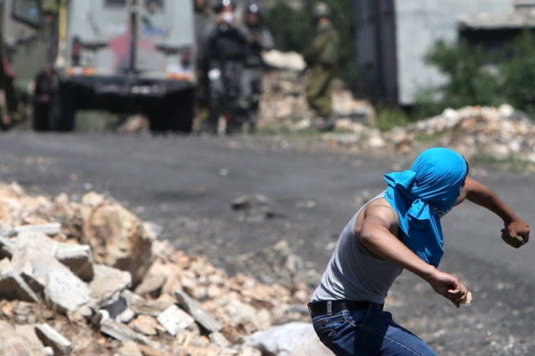 A Palestinian protester throws stones towards Israeli security forces during clashes in the occupied West Bank [AFP]