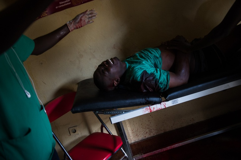 Pascal lies injured on a gurney in a small health centre in the Musaga neighbourhood, following clashes with police. He was injured by a gunshot, and later died. [Phil Moore/Al Jazeera]