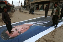 Fighters from a coalition of Islamist forces stand on a huge portrait of Syrian President Bashar al-Assad in Idlib [AFP]