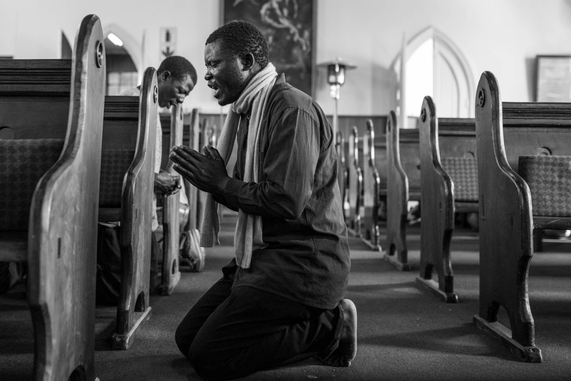 Displaced migrants from Malawi are seen on their knees as they pray for their safety at the Christ Church in the Johannesburg suburb of Mayfair. The premises of the church was used to set up a temporary camp for immigrants displaced by the recent xenophobic violence. [Ihsaan Haffejee/Al Jazeera]