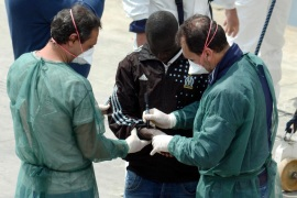 Italian officials apply identification marks to the hand of one of 84 migrants recently rescued [EPA]