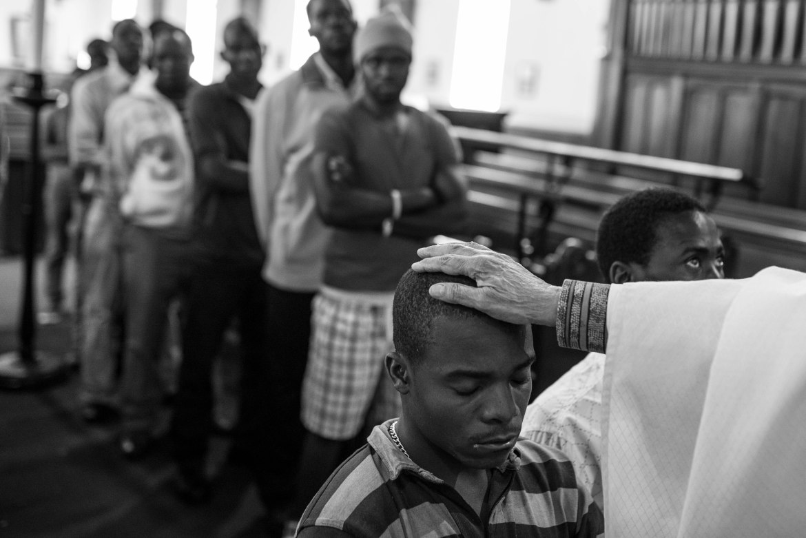 Reverend Eve Abrahams places her hand on the head of a displaced migrant from Malawi as she prays for his safety at the Christ Church. [Ihsaan Haffejee/Al Jazeera]