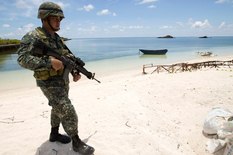 A Filipino soldier patrols Pag-asa Island in the disputed Spratlys in the South China Sea [AP]
