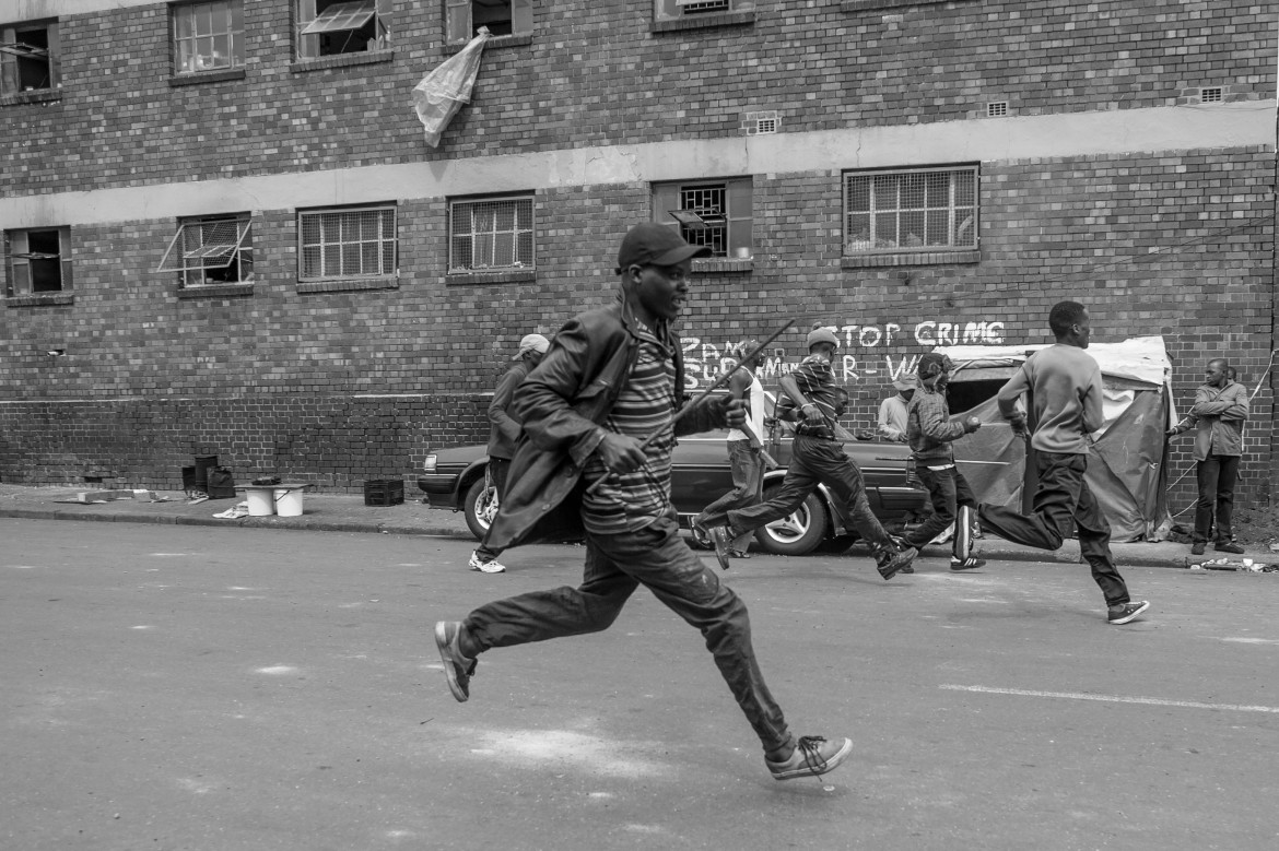 Men from the Jeppestown hostel run for cover as police fire rubber bullets to disperse the mob. [Ihsaan Haffejee/Al Jazeera]