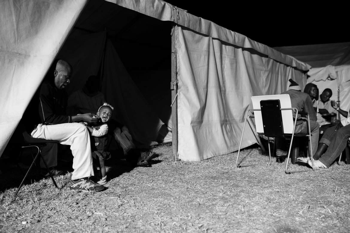 Jean Claude Dlamany, left, who hails from the Democratic Republic of Congo tries to feed his 18-month-old daughter L'or Dlamany supper at a camp set up in Johannesburg. Jean Claude was forced to flee from Umlazi in the province of KwaZulu-Natal with his family after the violence in that province spiralled out of control. He has lost almost all of his possessions and indicated that he will attempt to make a fresh start in Johannesburg as returning to the DRC is not an option for him due to the political situation over there. [Ihsaan Haffejee/Al Jazeera]