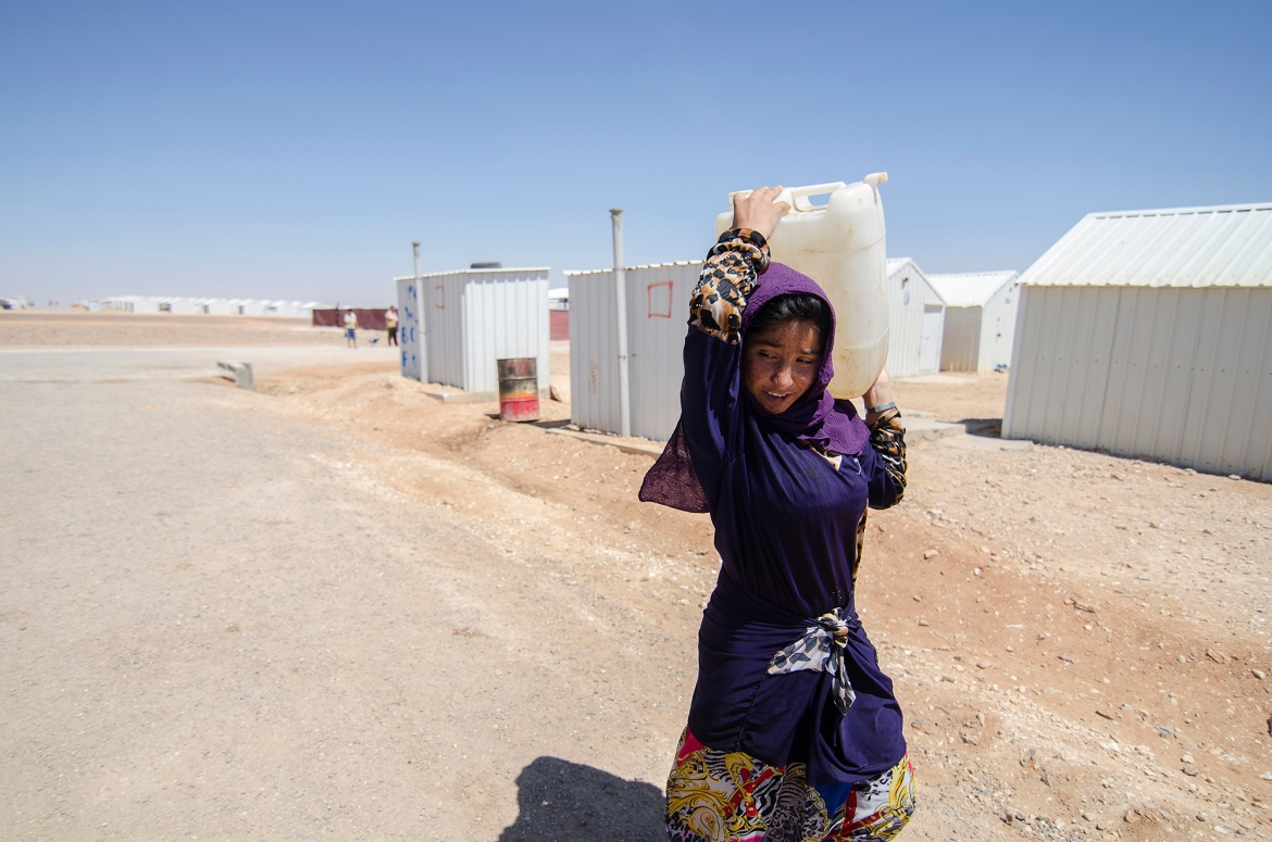 A young refugee carries water to her family's shelter in Azraq. Refugees say one of the main problems inside the desert camp is the scorching summer heat and a lack of electricity at night. [Alisa Reznick/Al Jazeera]