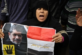 A supporter of the Muslim Brotherhood movement holds a placard showing Morsi during a demonstration in January [AFP]