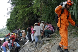 Miners and rescue workers carry sandbags as they try to prevent the gold mine from flooding [EPA]