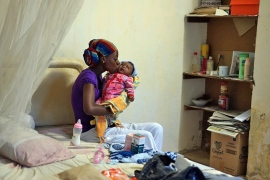 Jackie cradles her infant in a room at one of the sober houses [Abigail Higgins/Al Jazeera]