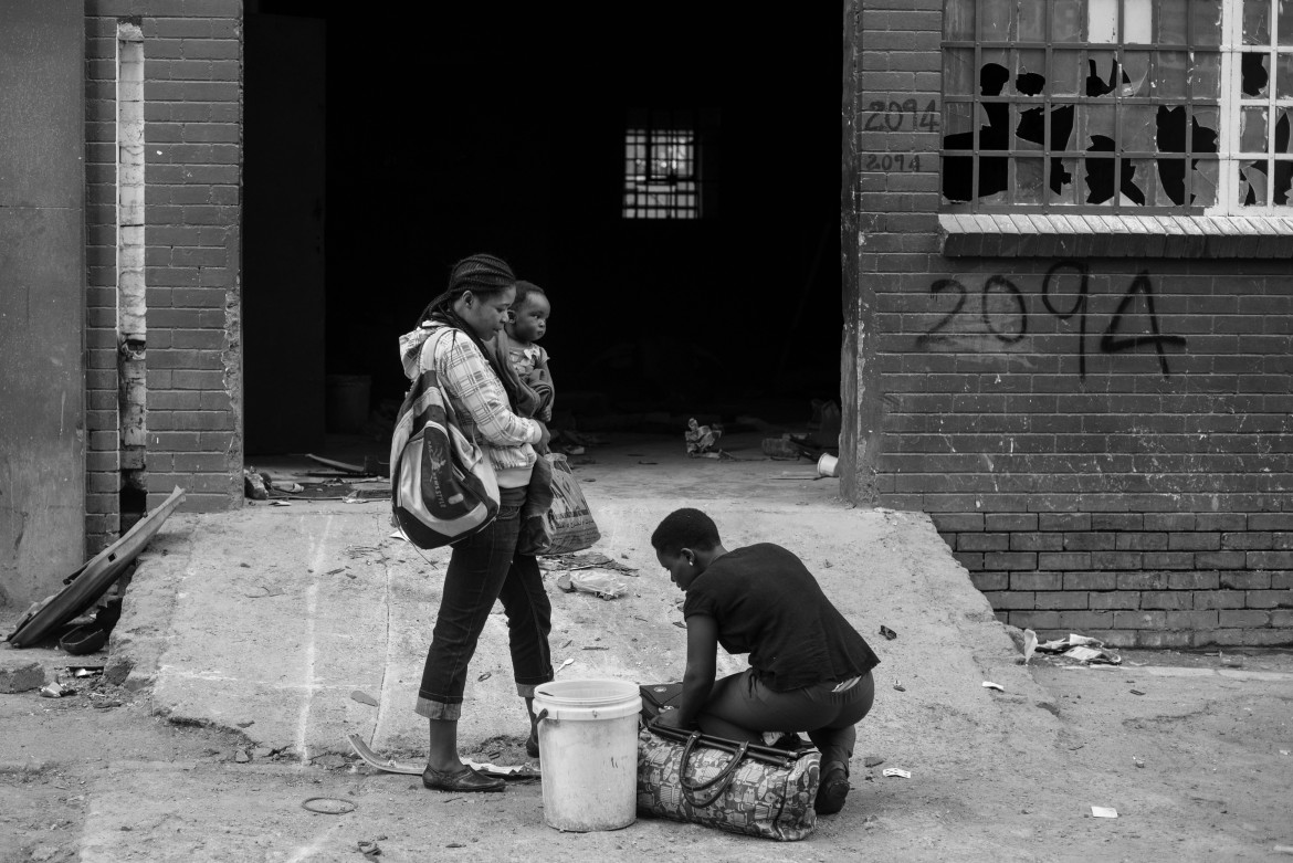 Migrant family pack their belongings as they prepare to flee the Jeppestown suburb after being threatened by locals. [Ihsaan Haffejee/Al Jazeera]