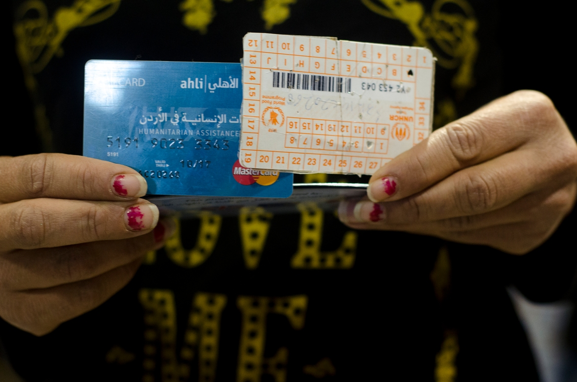 An Azraq resident displays her food voucher card. Each month, refugees receive the equivalent of $29 in food vouchers, but due to higher prices, they say it is often not enough. [Alisa Reznick/Al Jazeera]