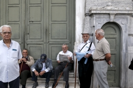 Pensioners wait for the opening of a National Bank branch to receive their monthly pensions in Athens [REUTERS]