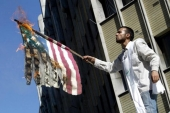 An Iranian hardliner wearing a death shroud burns a US flag outside the British embassy in Tehran in 2004 [Getty]