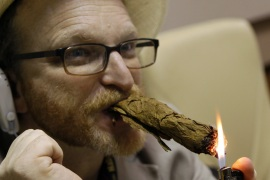 A man lights his self-made cigar during a rolling seminar in Havana, Cuba [EPA]