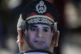A supporter of Egypt's Abdel Fattah el-Sisi wears a mask bearing his image [AFP]
