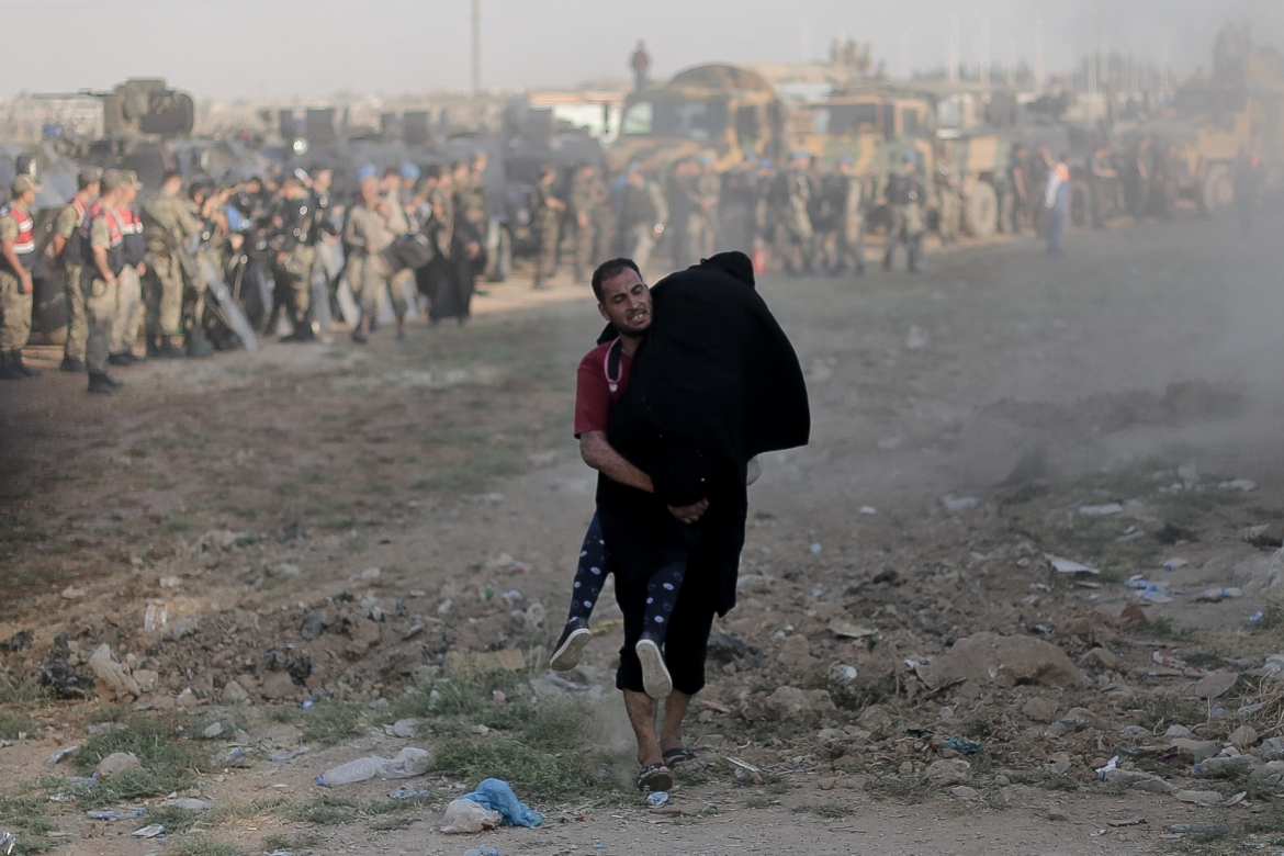 "A Syrian man carries a woman across the border. ""The international coalition is attacking ISIS positions. There is random shelling around petrol installations"" another man, Mohammed, who left Tal Abyad a week ago said. [Ahmed Deeb/Al Jazeera]"