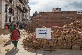 A resident passes by a sign for tourists in front of one of the collapsed temples in Basantapur Durbar Square in Kathmandu. [Omar Havana/Al Jazeera]
