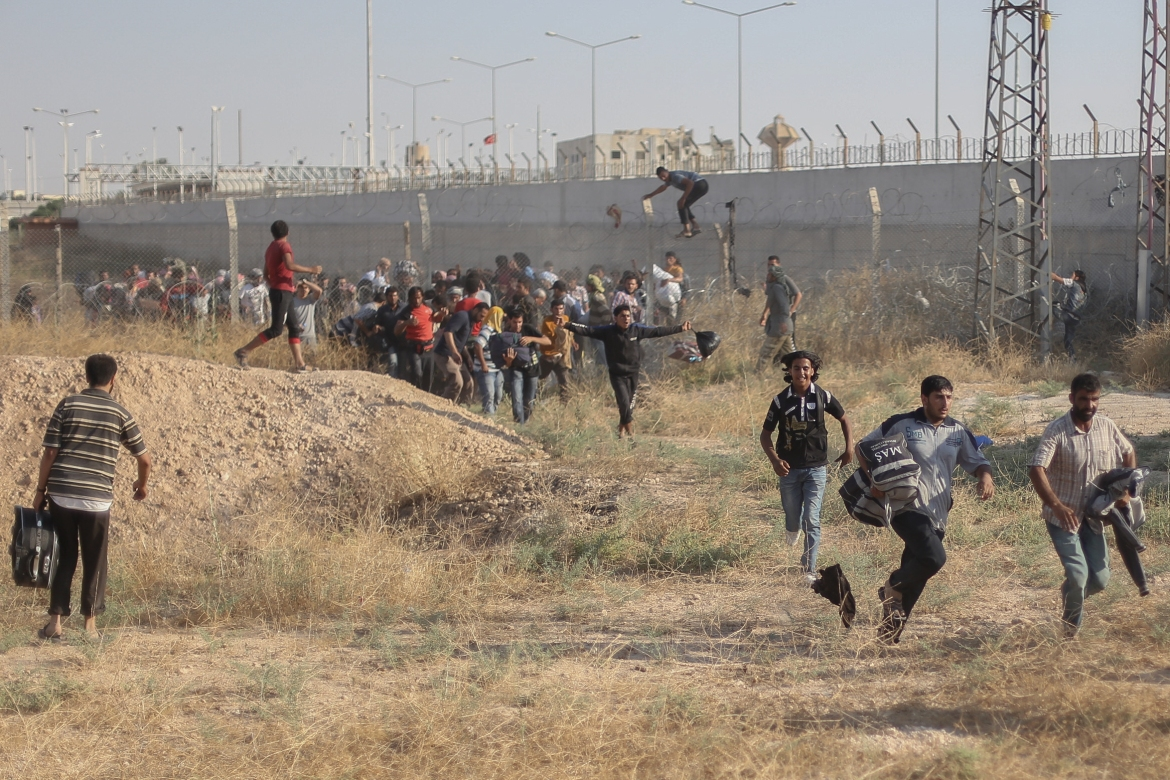 Syrian refugees break the border fence into southeastern Turkey. [Ahmed Deeb/Al Jazeera]