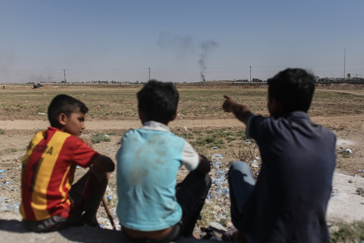 Syrian boys watch as smoke from a US-led air strike rises over the outskirts of Tal Abyad. [Ahmed Deeb/Al Jazeera]