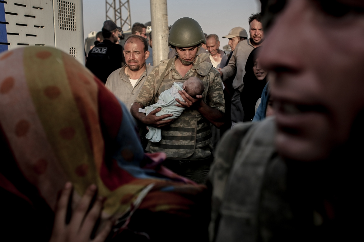 A Turkish soldier carries a Syrian baby across the border from Tal Abyad. [Ahmed Deeb/Al Jazeera]