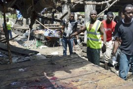 Rescue workers at the site of a suicide bomb attack at a market in Maiduguri, Nigeria in June 2015 [Jossy Ola/AP]