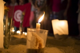 A lit candle in the sand in front of the Imperial Marhaba Hotel, where a gunman carried out an attack, in Sousse, Tunisia [REUTERS]