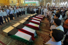 People pray in front of coffins draped with Kuwaiti flags belonging to victims of the Shia mosque bombing in Kuwait [AP]