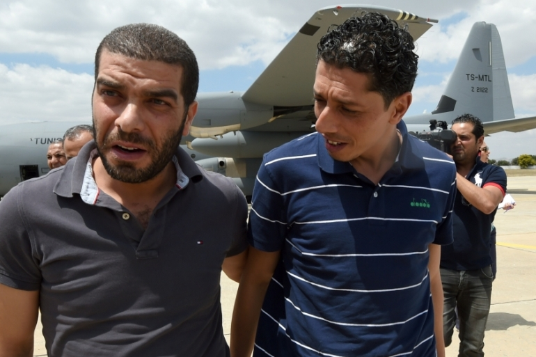 The freed employees flew to Tunis on Friday, calling their families to assure them they were 'doing well' [AFP]