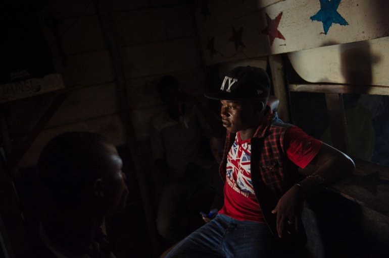 Ibrahim, 15, runs a mobile phone shop selling phone credit, in the gold mining town of Lugushwa. [Phil Moore/Al Jazeera]