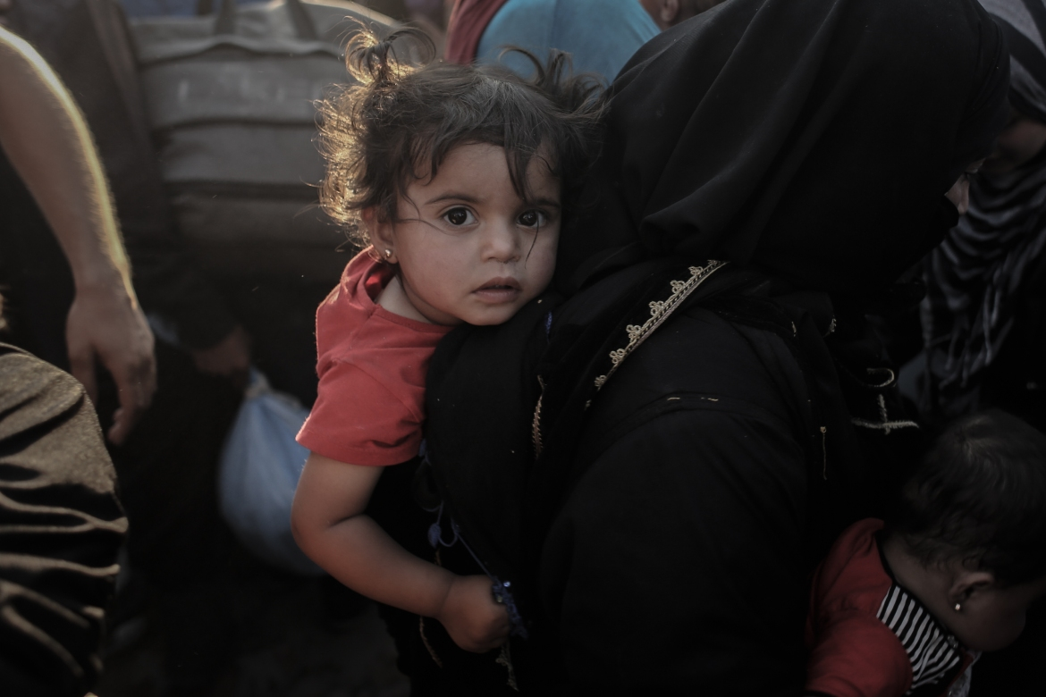 A Syrian woman carries her daughter while crossing the Akcakale border. [Ahmed Deeb/Al Jazeera]