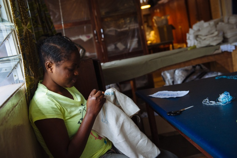 Darlene Confiance, 18, works as an embroiderer in the Kisany association. She must support her younger sister who is the only surviving member of her family. [Phil Moore/Al Jazeera]