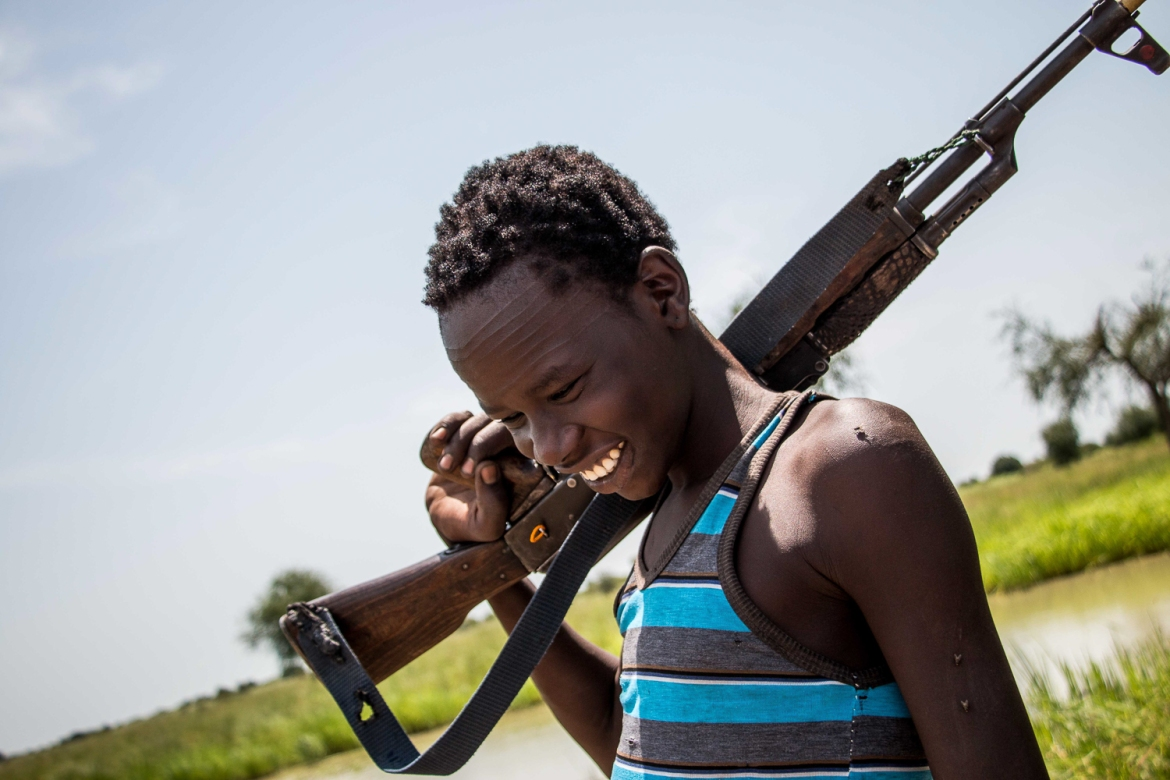 A young Nuer boy, with traditional facial scarification, carries his assault rifle near his home in Waat. [Ashley Hamer/Al Jazeera]