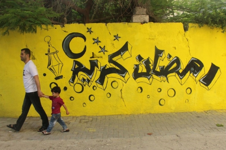 A year after a devastating war, local residents have gathered to paint walls and beautify their neighbourhood with messages of positivity [Walaa Ghussein/Al Jazeera]