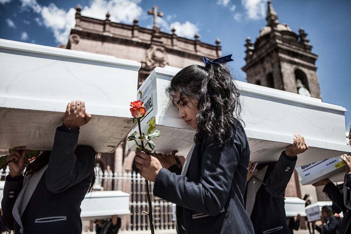 Family members and volunteers carry the coffins through the streets of Ayacucho. [Nadia Shira Cohen/ICRC]