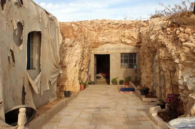 The entrance of this cave home was enlarged to place a door and a window. On the left, the family built a new brick house that is covered up by plastic, as Israel has prevented residents from building any new structure. [Eloise Bollack/Al Jazeera]