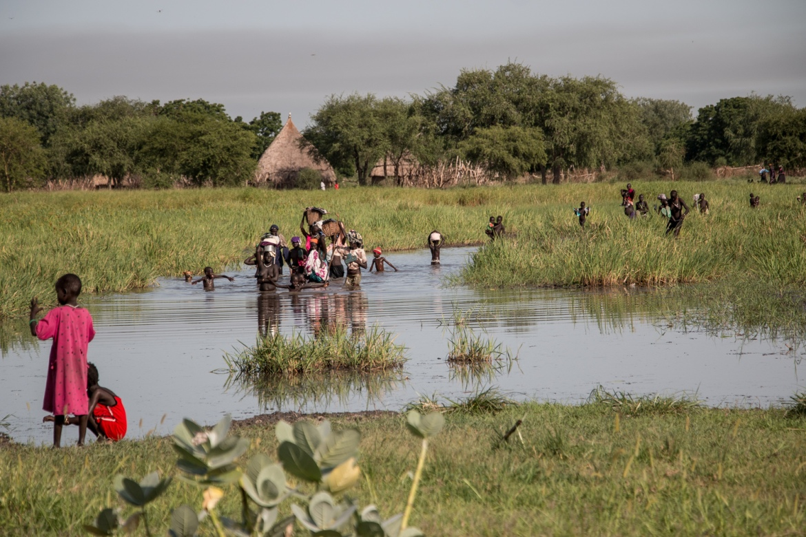 Thousands of people cross swampy waterways to reach the registration point [Ashley Hamer/Al Jazeera]