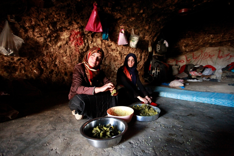 Saheer Hamamdi prepares dawali, a traditional Palestinian dish, with her sister-in-law. In cave dwellings, there is no proper kitchen and no table, so the food is prepared and eaten directly on the ground. [Eloise Bollack/Al Jazeera]